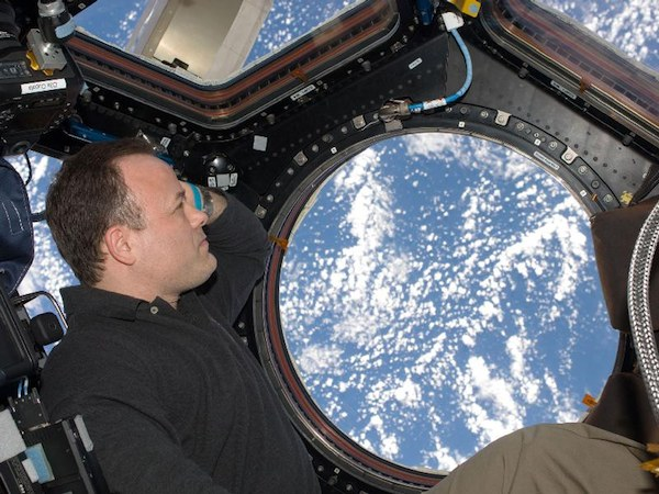 NASA astronaut Ron Garan gazes at Earth from the International Space Station. Research indicates long-duration spaceflights may negatively impact eyesight. (Credits: NASA).