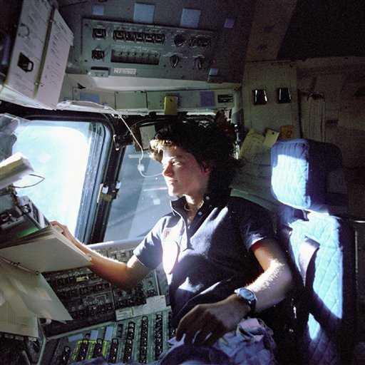 Sally Ride monitors control panels from the pilot's chair on the shuttle flight deck (Credits: NASA).