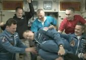 ISS crew help astronaut Tom Marshburn turn a quick flip at his daughter's request (Credits: NASA).