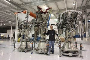 Tom Muelle rwith his Merlin engines as SpaceX headquarters (Credits: Roger Gilbertson/Tom Mueller).
