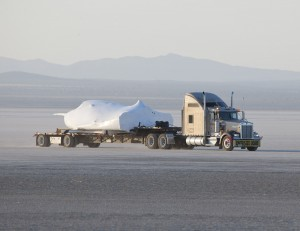 SNC's Dream Chaser test flight craft is hauled across the bed of Rogers Dry Lake at Edwards Air Force Base, Calif., to NASA's Dryden Flight Research Center on May 15. Image credit: NASA/Tom Tschida