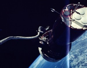 A view of Gemini IX-A, including its maneuvering thrusters, taken by Gene Cernan. His lengthy tether is clearly visible (Credits: NASA).