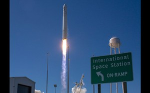 "Cygnus launches behind the ISS ""onramp"" road sign at Wallops Island (Credits: NASA)."