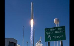 """Cygnus launches behind the ISS """"onramp"""" road sign at Wallops Island (Credits: NASA)."""