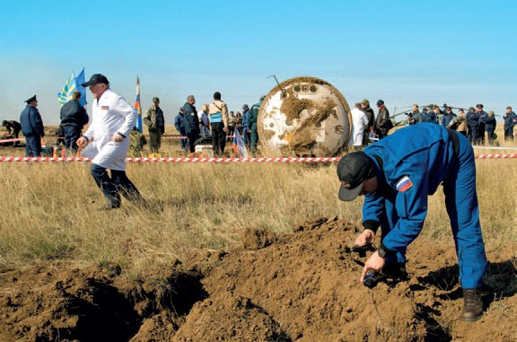 A Russian ground crew member examines the over turned soil near the Soyuz TMA-11 spacecraft after it landed (Credits: NASA).