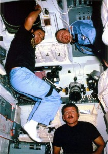 In one of relatively few images ever publicly released from Mission 51C, astronauts Loren Shriver (bottom), Ellison Onizuka (left), and Jim Buchli pose for a photograph in Discovery's flight deck (Credits: NASA).