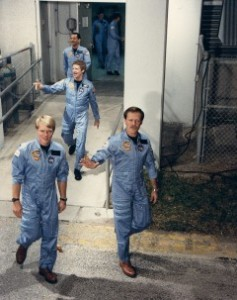 "Robert ""Hoot"" Gibson (right) and George ""Pinky"" Nelson lead the 61C crew out of the Operations & Checkout Building for launch. Following is crewmate Steve Hawley (Credits: NASA)."
