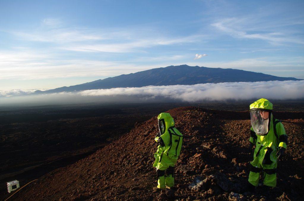 HI-SEAS crew members in environmental suits outside habitat