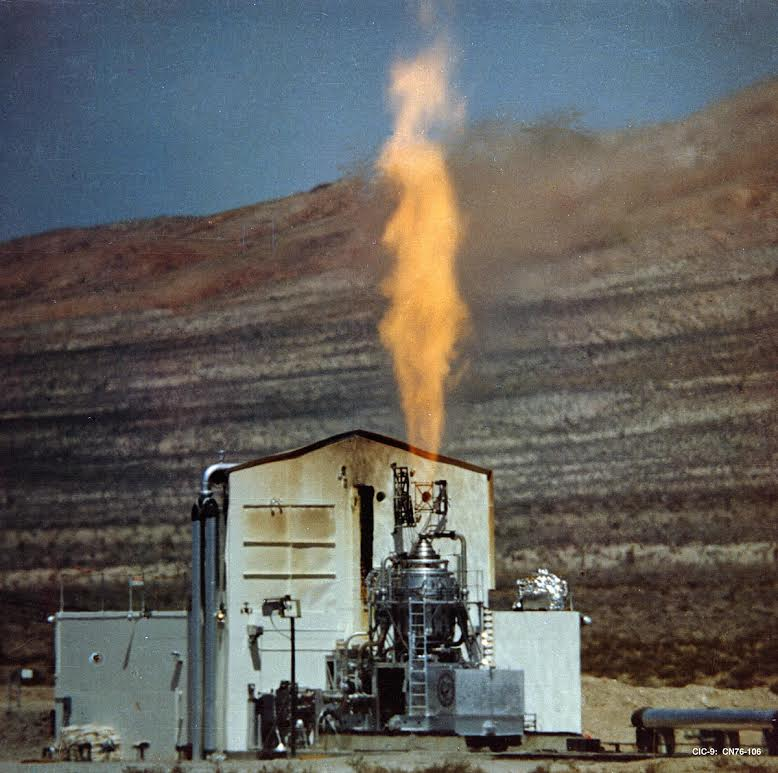 The Rover Kiwi-A full power test conducted at Jackass Flats located on the Nevada Test Site on July 1, 1959. The hydrogen exhaust plume that blurs out the mountains in the background is mostly invisible and dwarfs the visible central column. (NASA)