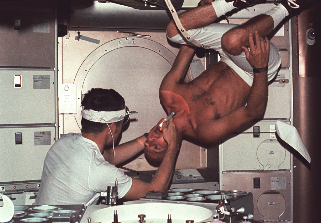 Skylab 1 commander Pete Conrad undergoes a dental examination by medical officer Joseph Kerwin