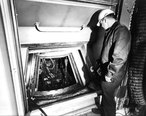 Dale Carothers, Spacecraft Operations Directorate, in the white room, looking at the interior of the AS-204 capsule through the open hatch
