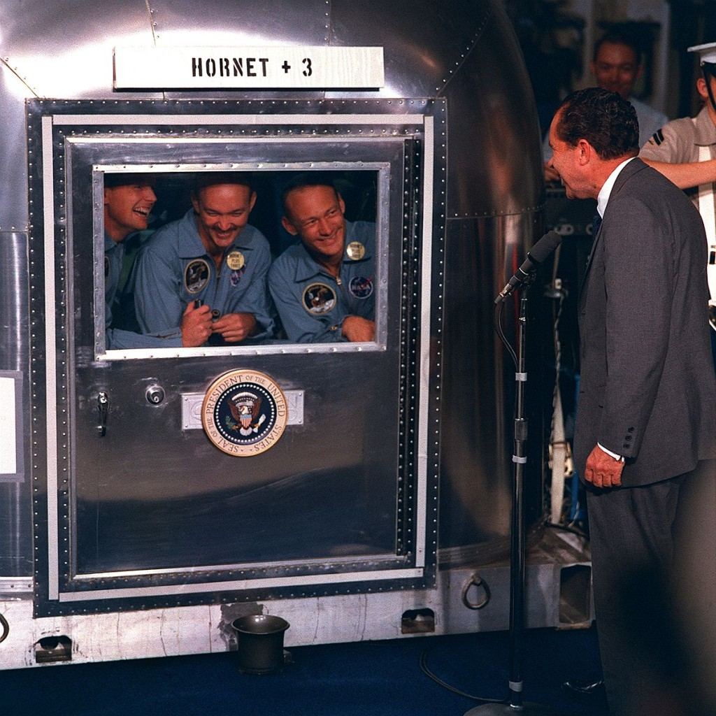 Caption: Apollo 11 astronauts Neil Armstrong, Buzz Aldrin, and Michael Collins talk with Pres. Nixon from the Mobile Quarantine Facility, an anti-contamination measure devised to prevent backward contamination from the Moon. – Credits: NASA.