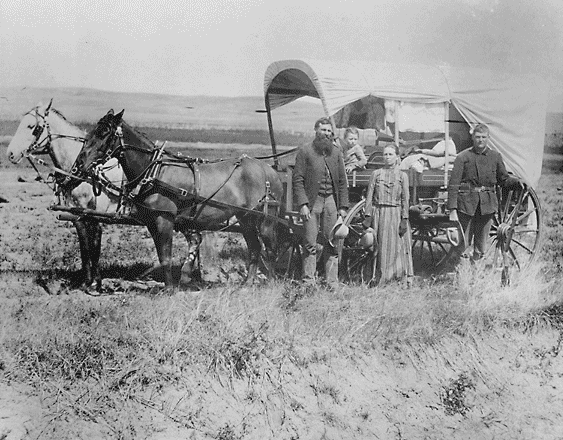 A family poses with the wagon in which they live and travel daily during their pursuit of a homestead. - Credits: NARA - ARC Identifier 518267.