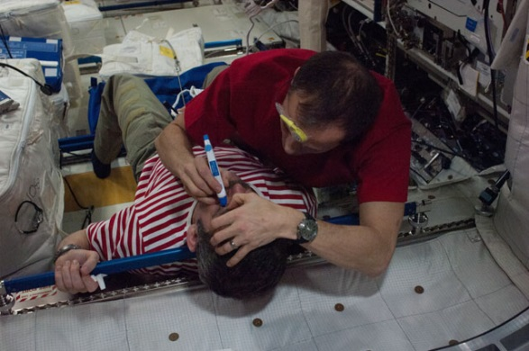 Expedition 34/35 Flight Engineer Tom Marshburn of NASA performs a tonometry eye exam on Chris Hadfield of the Canadian Space Agency in the Columbus module of the International Space Station. Tonometry measures intraocular eye pressure. Credits: NASA