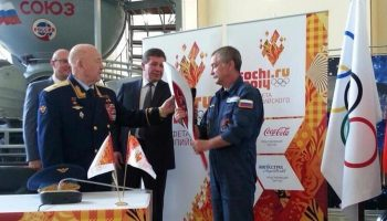 Former cosmonaut Alexey Leonov, left, the first man to perform a spacewalk, passed an Olympic Torch to Mikhail Tyurin, flight engineer of Expedition 38/39 (Credits: Dmitry Chernyshenko).